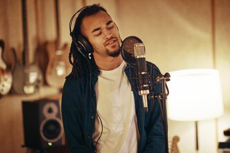 Jonge Afro-Amerikaanse muzikant die in een microfoon zingt terwijl hij tracks neerlegt in een muziekstudio Stockfoto