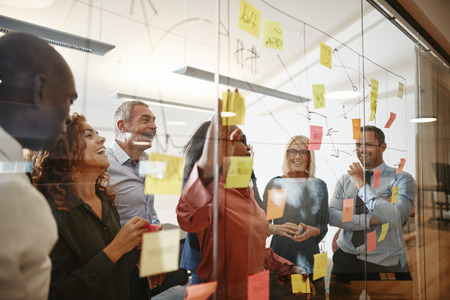 젊은 아프리카 여성 사업가와 그녀의 다양한 팀은 현대적인 사무실의 유리벽에 스티커 메모로 브레인스토밍 세션을 하는 동안 웃고 있습니다.