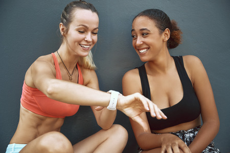 Fit young woman in sportswear showing her workout partner her sports watch while sitting on the pavement outside after a run together