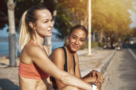 Smiling young woman in sportswear sitting on a curb with her workout partner taking a break from their run