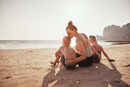 Loving Mother kissing her little boy on the head while sitting with her daughter on a sandy beach during summer vacation