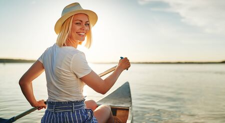 Smiling young blonde woman looking back over her shoulder while paddling a canoe on a scenic lake on a summer afternoon