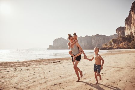 Laughing mother piggybacking her little daughter while running with her son along a sandy beach during summer vacation