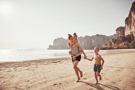 Madre ridente che trasporta sulle spalle la sua piccola figlia mentre corre con suo figlio lungo una spiaggia sabbiosa durante le vacanze estive