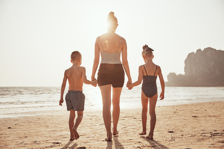 Rearview of a two children and their Mom walking hand in hand together along a sandy beach during summer vacation Banco de Imagens
