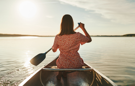 Rearview of a young woman looking at the horizon while paddling a canoe on a still lake on a sunny afternoon