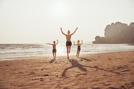 Rear view of a Mother and her two small children skipping together with their arms in the air along a sandy beach during summer vacation Reklamní fotografie