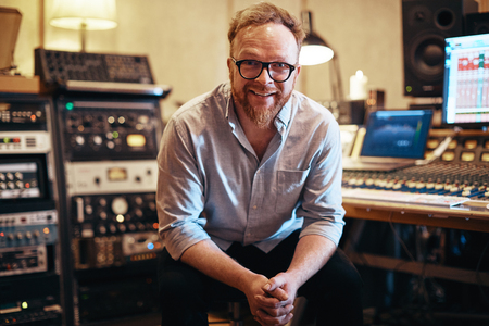 Smiling mature music producer sitting in his recording studio surrounded by sound and audio equipment