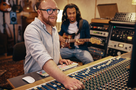 Smiling music producer making adjustments on a soundboard with an African American musician playing guitar in the background