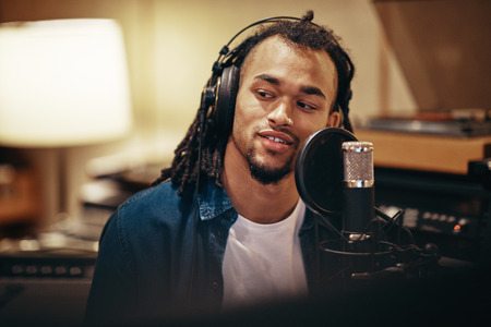 Smiling young African American singer wearing headphones sitting in a recording studio preparing to lay down tracks