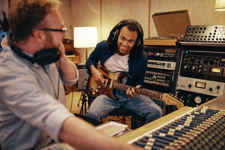 Smiling young African American guitarist and music producer working on together on a track in a recording studio Stock Photo