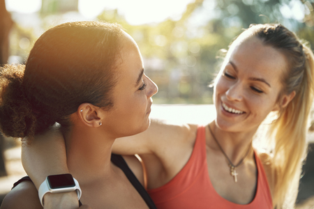 Two fit young women in sportswear laughing while standing arm in arm together outside on a sunny day before their workout