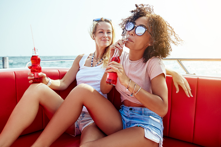 Two smiling young female friends having drinks while sitting together on a boat on the open ocean during summer vacation 写真素材