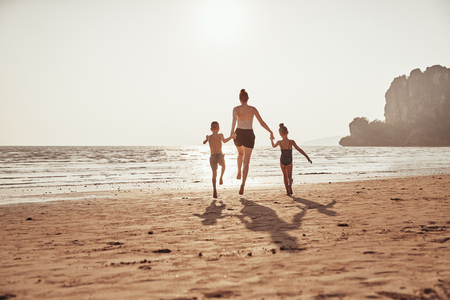 Rearview of a Mother and her two small children skipping hand in hand together along a sandy beach during summer vacation