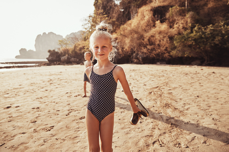 Cute little girl in a swimsuit smiling while standing on a sandy beach with her mother and brother walking in the background
