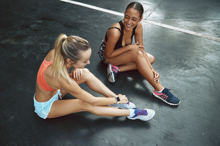 High angle of two fit young women in sportswear sitting in a parking lot outside talking and laughing together Stock Photo