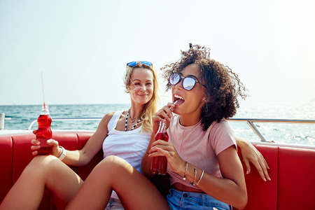 Laughing young woman sipping on a drink while relaxing on a boat on the ocean with a friend during their summer vacation