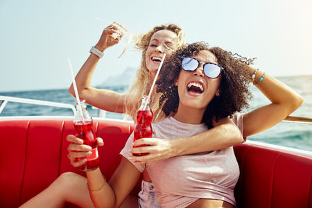 Two young female friends laughing and having drinks together while sitting on a boat on the open ocean during summer vacation 写真素材