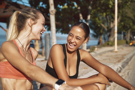 Two fit young women in sportswear stting on a curb talking and laughing while taking a break from their run Stock Photo