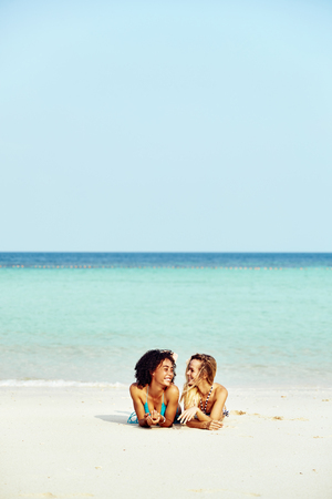 Two laughing young female friends wearing bikinis suntanning together on a sandy beach during a tropical vacation Stock Photo