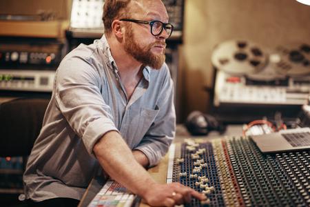 Volwassen muziekproducent die aanpassingen maakt aan zijn audioapparatuur terwijl hij in een geluidsopnamestudio werkt Stockfoto