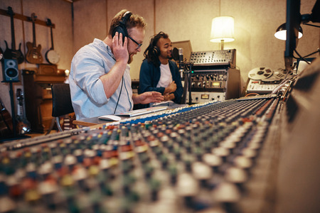 Music producer working on a soundboard while listening to a young African American singer in a recording studio Stock Photo