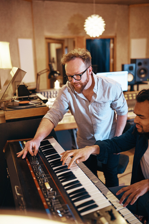 Music producer working with a young African American musician playing the keyboards in a recording studio