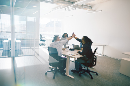 Diverse group of work colleagues laughing and high fiving together while sitting around a table inside of a glass walled office
