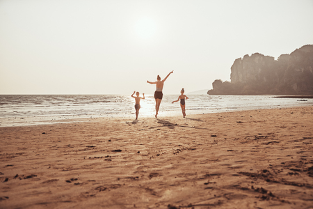 Rearview of a Mom and her two little children skipping together with their arms in the air along a sandy beach during summer vacation