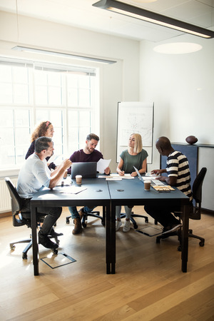 Diverse group of young designers discussing work together while sitting around a boardroom table in an office