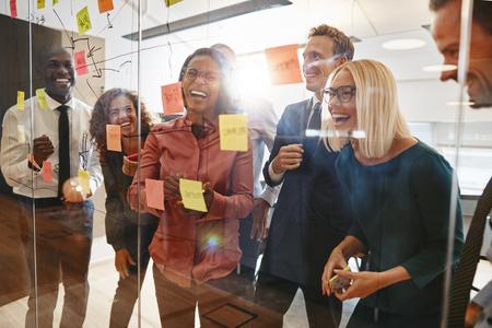 Riendo el grupo de diversos empresarios que tienen una sesión de intercambio de ideas junto con notas adhesivas en una oficina.