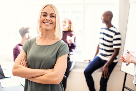 Smiling young female designer standing confidently with her arms crossed after a boardroom meeting with colleagues standing in the background