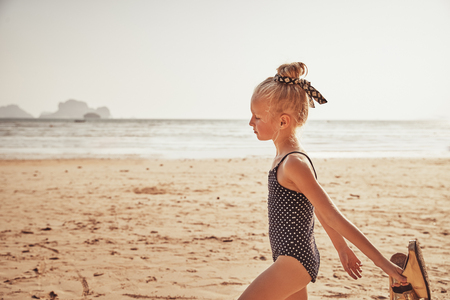 Adorable little girl in a swimsuit walking along a sandy beach carrying her sandals during summer vacation
