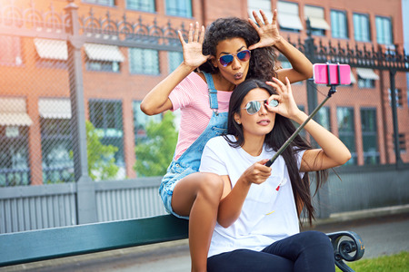 Two smiling young women making faces while sitting on a city bench taking self portraits together with a smartphone and selfie stick