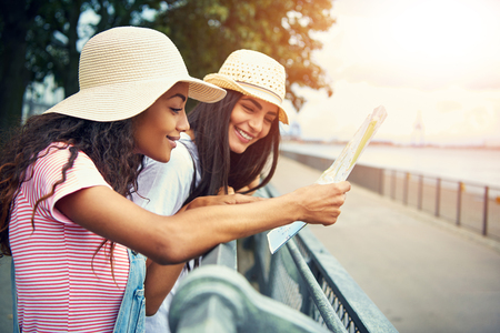 Smiling diverse female friends look at a map while wearing light colored straw hats