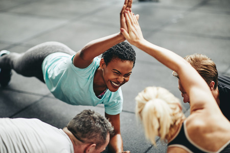 Two fit young women in sportswear laughing and high fiving while planking with a couple of male friends on the floor of a gym Foto de archivo