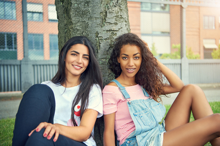 Pair of beautiful young adult women sitting next to each other under tree near urban apartment building outdoors Stock Photo