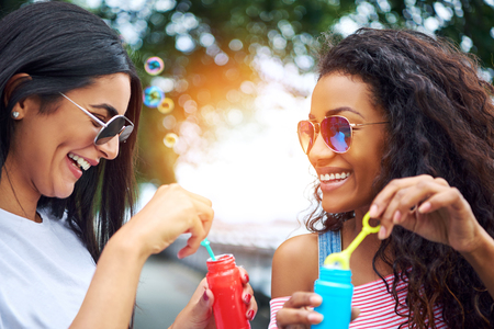 Two laughing young girlfriends having fun blowing bubbles with a toy bubble wand while enjoying a sunny day together outdoors Stockfoto