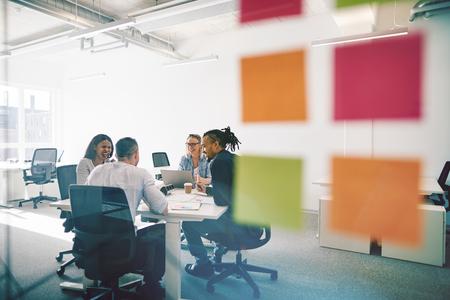 Primer plano de notas adhesivas en la pared de vidrio de una oficina con un grupo diverso de compañeros de trabajo que tienen una reunión alrededor de una mesa
