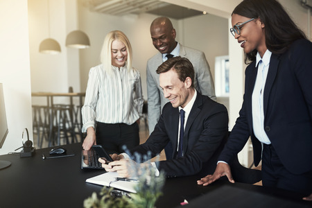 Laughing group of diverse businesspeople watching an office colleague playing a cellphone game while sitting at his desk after work Фото со стока