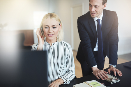 Smiling young businesswoman discussing scheduling with a client over a headset while working at her office desk with a coworker standing behind her Standard-Bild