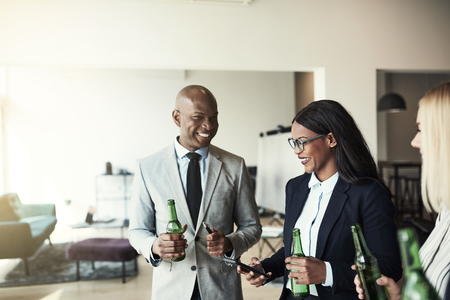 Smiling young African American businesswoman showing a coworker photos on her cellphone while having drinks in an office after work
