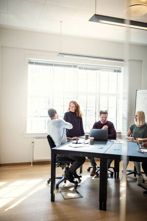 Two smiling designers shaking hands while working around a boardroom table with colleagues inside of an office