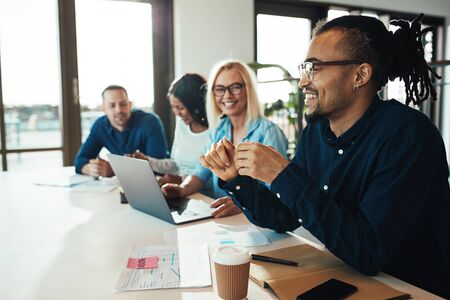 Young African American office worker laughing while sitting with a diverse group of colleagues during a meeting Stock Photo