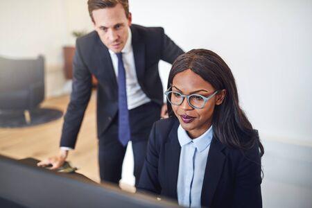 Joven empresaria afroamericana que trabaja con un colega en una computadora en su escritorio en una oficina.