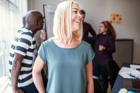 Young female designer laughing while standing in an office after a meeting with colleagues standing in the background Banque d'images