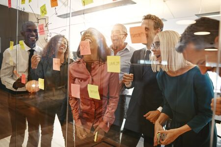 Diverse group of businesspeople laughing together during a brainstorming session with sticky notes on a glass wall in a modern office