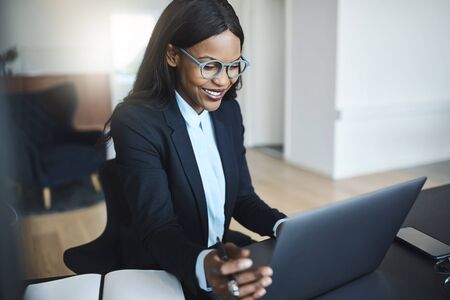 Smiling young African American businesswoman working on a laptop while sitting alone at her desk in a bright modern office Foto de archivo