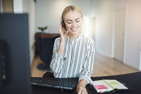 Smiling young businesswoman wearing a headset and talking with a client while working on a computer and reading her day planner in an office Stock Photo