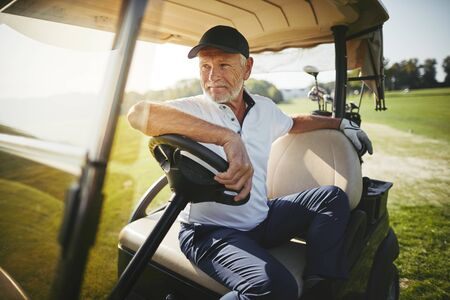 Smiling senior man sitting in a golf cart looking out at the fairway while playing a round of golf on a sunny day 写真素材